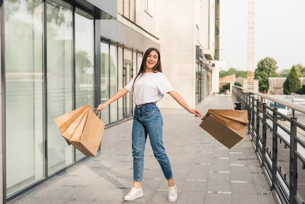 Bella donna felice con i sacchetti della spesa variopinti in mano che salta allegramente nell'aria.