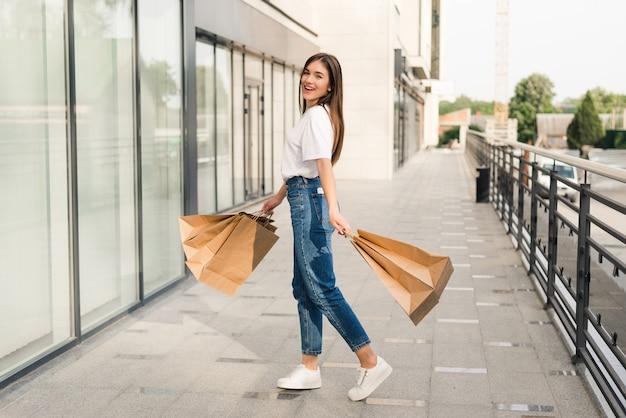 カラフルな買い物袋を手に元気に空中ジャンプする幸せな美しい女性。