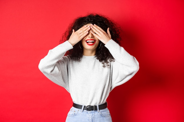 Happy beautiful woman with curly hair and red lips, covering eyes with hands and waiting surprise, smiling excited, standing against red background.