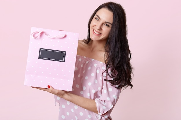 Happy beautiful woman with dark hair, dressed in polka dot dress, holds gift bag with present, has positive facial expression