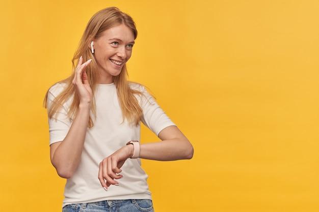 Bella donna felice con le lentiggini in maglietta bianca che ascolta la musica con gli auricolari senza fili e utilizza orologio intelligente su giallo