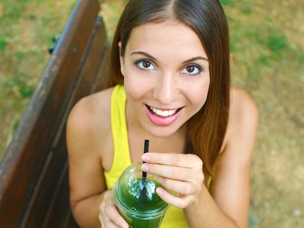 緑のスムージーと幸せな美しい女性