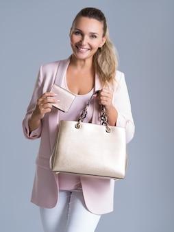 Счастливая красивая женщина с сумочкой и бумажником в покупках