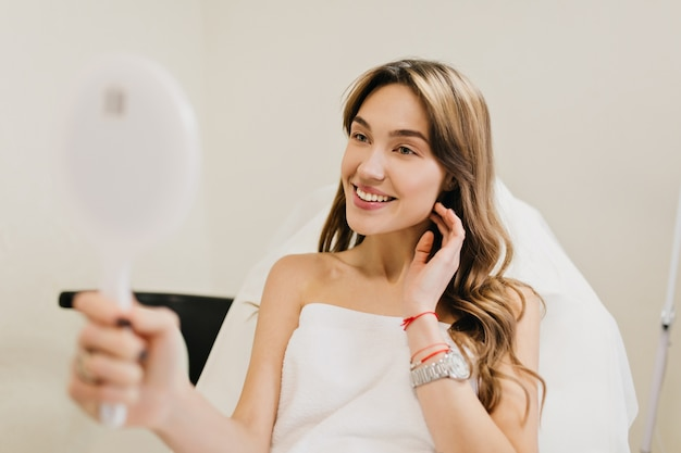 Happy beautiful woman with long brunette hair after cosmetology therapy smiling to mirror in white room. joy, happines, good results, true positive emotions