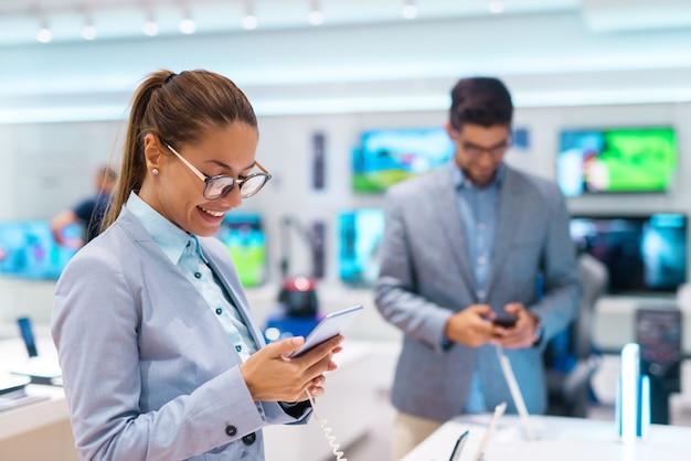 Счастливый красивая женщина с хвостиком и одетый в костюм, покупая новый смартфон
