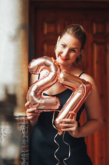 Happy beautiful woman with red lipstick in a black dress holding rose gold balloons