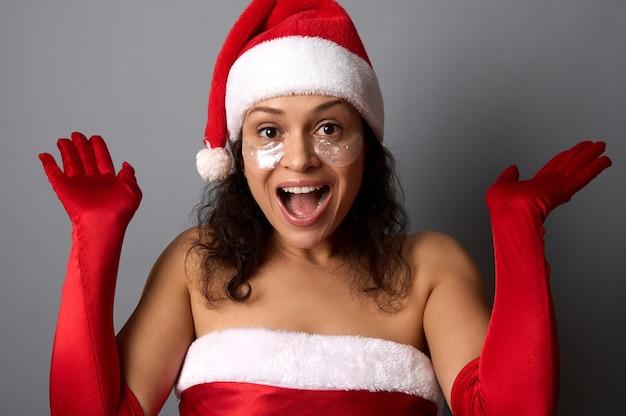 目の下に光沢のある滑らかな眼帯を持つ幸せな美しい女性は、サンタの服を着て、手のひらを上に置き、カメラを見て喜んでいます。メリークリスマス、新年と美容の概念