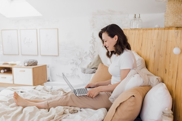 Happy beautiful woman working on a laptop while sitting on a bed in a bright modern house