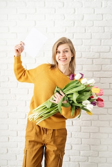 Happy beautiful woman in yellow clothes holding bouquet of tulips and blank card