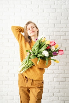 Happy beautiful woman in yellow clothes holding bouquet of tulips