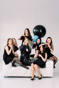 Happy beautiful women celebrating birthday or hen party, sitting on white sofa indoor and blowing soap bubbles. birthday party, balloons, holiday