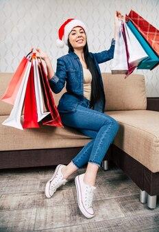 쇼핑백과 함께 소파에 앉아 산타 모자에 행복 한 아름 다운 여자