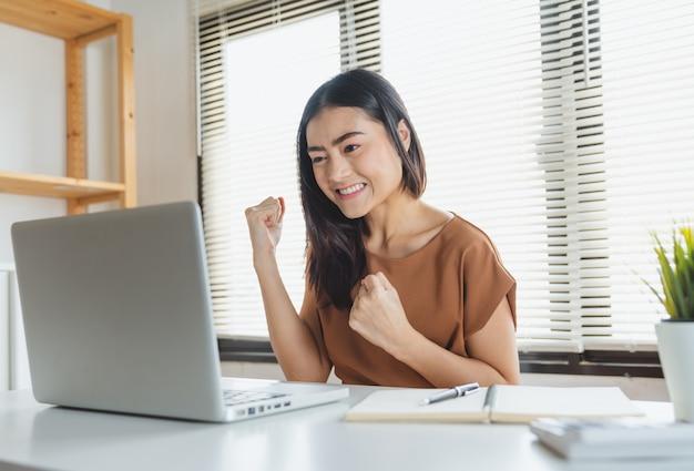 Счастливая красивая молодая азиатская возбуждающая женщина подняла ее руку с онлайн заказами от клиентов в компьтер-книжке. концепция продукта продавца онлайн.
