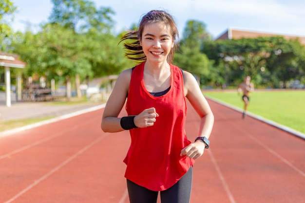 Happy beautiful young asian woman in red exercise outfit running in the morning