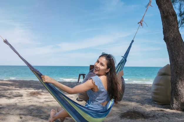 Happy beautiful young asian woman sitting on hammock at the beach on vacation