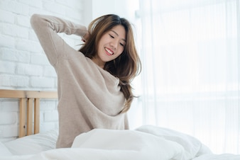 Happy beautiful young Asian woman waking up in morning, sitting on bed, stretching in cozy bedroom