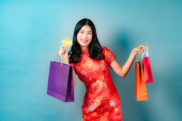 Счастливая красивая молодая азиатская женщина носит красное китайское традиционное платье с рукой, держащей кредитную карту и хозяйственные сумки на синем