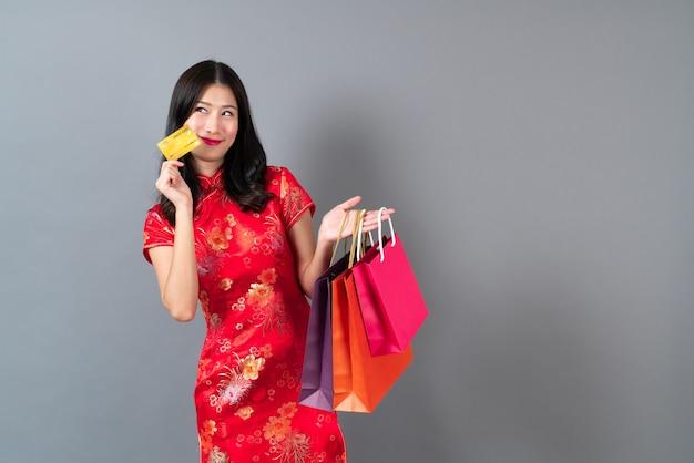 Счастливая красивая молодая азиатская женщина носит красное китайское традиционное платье с рукой, держащей кредитную карту и хозяйственные сумки на сером