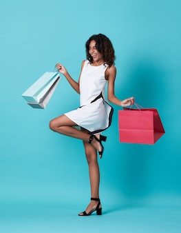 Happy beautiful young black woman in white dress and hand holding shopping bag