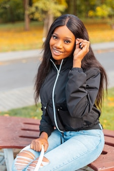 Happy beautiful young black woman with a smile in a fashionable casual jacket with jeans sits on a bench in an autumn park with yellow foliage