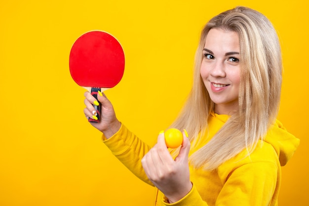 カジュアルな黄色のスポーティな服を着た幸せな美しい若いブロンドの女性は、ボールとラケットを持って卓球をします。