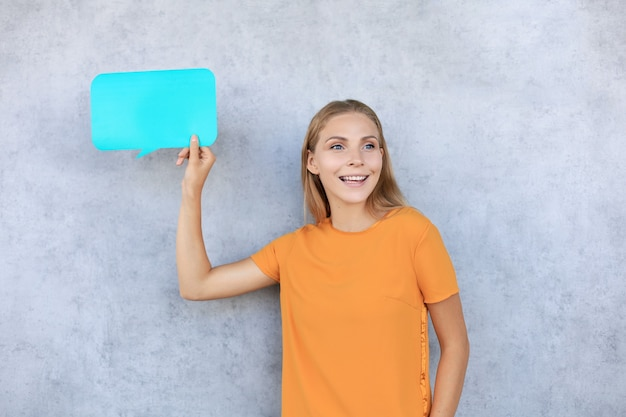 Happy beautiful young blonde woman standing isolated over gray background, holding empty speech bubble.