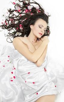 Счастливая красивая молодая брюнетка девушка покрыта простыней в яркие цветы, изолированных на белом