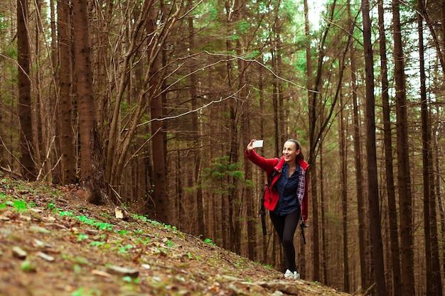 ハイキングしながらスマートフォンで幸せな美しい若いブルネットの女性が山の上に歩いています。