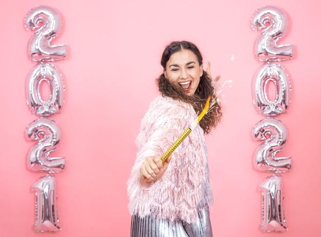 Счастливая красивая молодая брюнетка с вьющимися волосами в праздничном наряде с фейерверк-свечой в руке на розовой стене с серебряными шарами для новогодней концепции