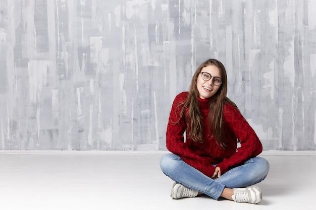 眼鏡、ジーンズ、居心地の良いセーター、スニーカーを身に着けている幸せな美しい若い白人女性は、床に足を組んで座って、広い陽気な笑顔で見て、白い歯を振る