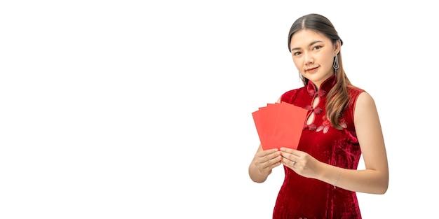 赤いお金の封筒を保持している赤い中国のドレスで幸せな美しい若い中国人女性