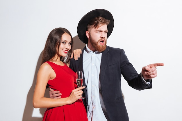 Happy beautiful young couple drinking champagne and pointing away over white background