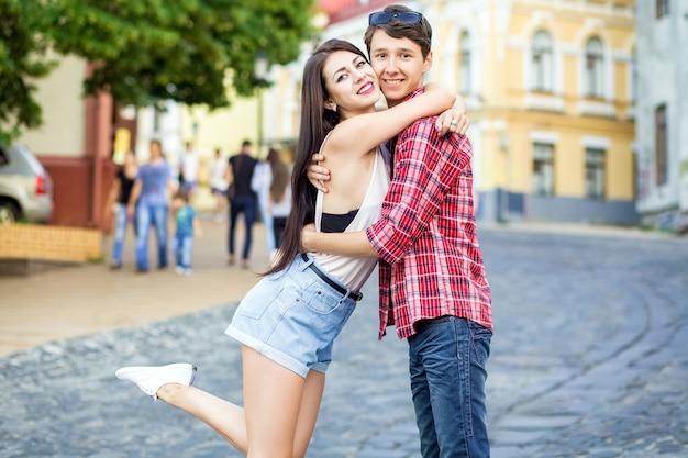 Счастливая красивая молодая пара в любви обниматься и веселиться вместе в городе в летний день