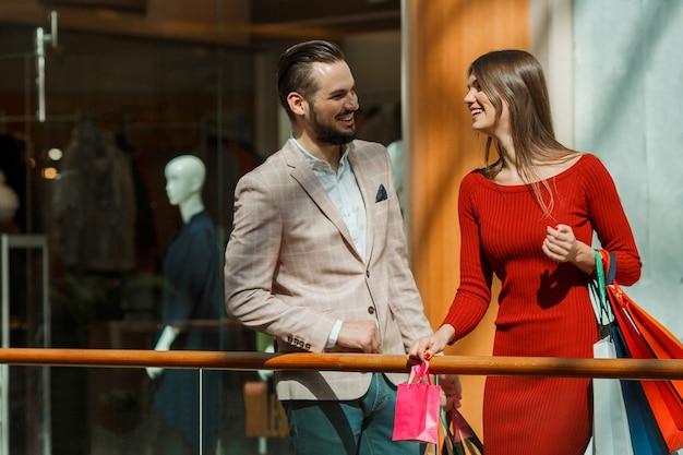 Счастливая красивая молодая пара с хозяйственными сумками в торговом центре