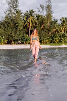 Felice bella giovane donna europea con una bottiglia di plastica di acqua in mano in spiaggia
