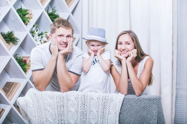 Счастливая красивая молодая семья, отец, мать и дочь, улыбаются вместе дома
