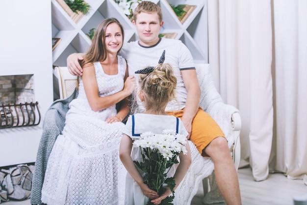 Счастливая красивая молодая семья, отец, мать и дочь дарят букет цветов, улыбаясь вместе дома