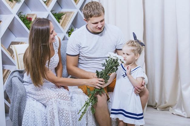 행복한 아름다운 젊은 가족 아버지 어머니와 딸이 함께 웃고 있는 꽃다발을 줍니다