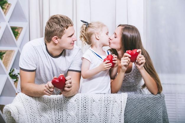 Счастливая красивая молодая семья, отец, мать и дочь с красными сердцами, улыбаются вместе дома