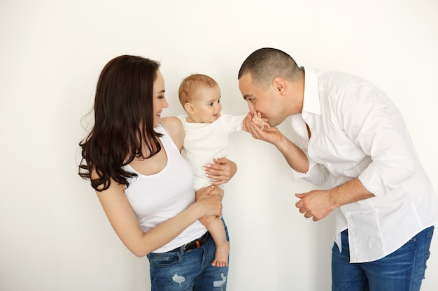 Happy beautiful young family with baby smiling embracing posing over white wall.