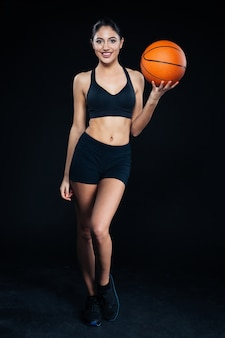 Happy beautiful young fitness girl standing and holding basketball ball over black background
