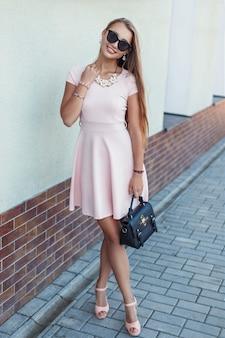 Счастливая красивая молодая девушка в розовом платье с черной сумкой у стены