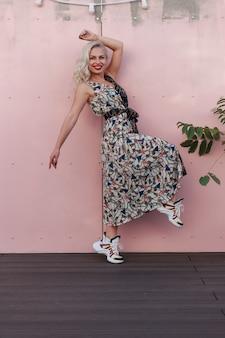 Счастливая красивая молодая девушка в модном платье прыгает возле розовой стены
