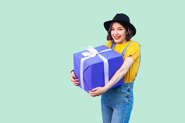 세련된 힙스터를 입은 행복한 아름다운 소녀는 데님 작업복을 입고 검은 모자를 쓰고 이빨 미소로 크고 무거운 선물 상자를 들고 카메라를 바라보고 있습니다. 스튜디오 촬영, 녹색 배경