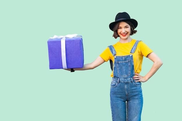 힙스터를 입은 행복한 아름다운 소녀는 데님 작업복을 입고 검은 모자를 쓰고 벨트에 손을 대고 큰 무거운 선물 상자를 들고 카메라를 바라보고 있습니다. 스튜디오 촬영, 녹색 배경
