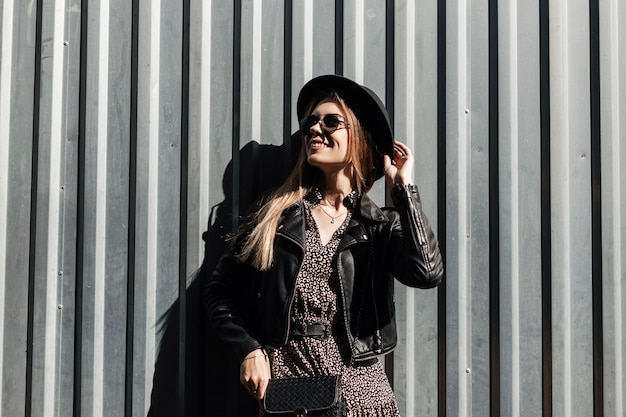 Счастливая красивая молодая девушка-модель с милой улыбкой, модными солнцезащитными очками и шляпой в черной кожаной куртке и винтажном платье стоит у металлической стены в солнечный день