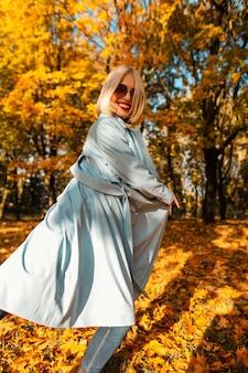 動きのあるファッショナブルな青いコートにサングラスをかけたかわいい笑顔の幸せな美しい少女は、黄色の葉のある秋の公園を歩きます。秋の晴れた休暇の日の女性の面白い感情