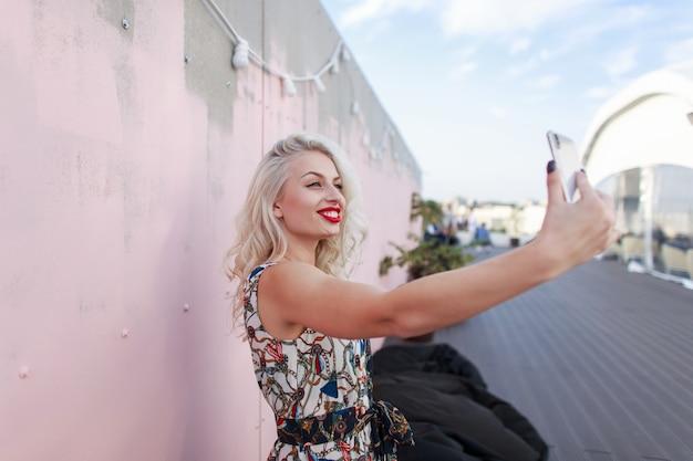 세련된 빈티지 드레스에 미소로 행복한 아름다운 어린 소녀가 파티에서 분홍색 벽 근처에 전화로 사진을 찍습니다.