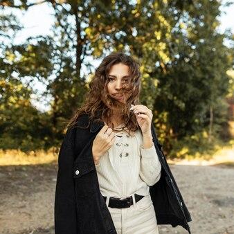 나무 배경에 자연에 니트 블라우스를 입은 세련된 데님 재킷에 곱슬머리를 한 행복한 아름다운 소녀