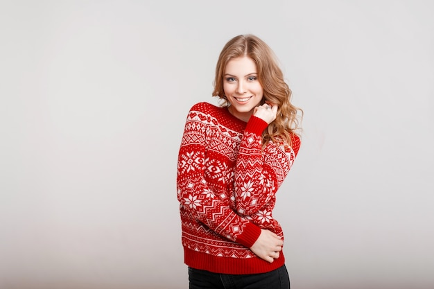 Happy beautiful young girl with cute smile in vintage red sweater on gray background